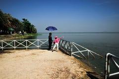 Fütterungsfische der Großmutter und der Enkelin das Lebensmittel am See lizenzfreie stockfotografie