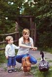 Fütterungshuhn und Ente der Familie auf Wiese Lizenzfreie Stockfotografie