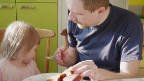 Fütterungskind des Vaters, das Aufmerksamkeit erregt, um zu Hause zu löffeln stock video footage