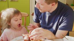 Fütterungskind des Vaters, das zu Hause Aufmerksamkeit zur Nahrung erregt stock video