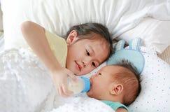 Fütterungsmilch der entzückenden asiatischen älteren Schwester von der Flasche für das neugeborene Baby, das auf dem Bett liegt stockfotos