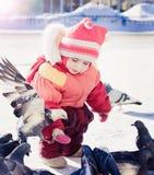 Fütterungstauben des kleinen Mädchens im Winter Lizenzfreies Stockbild