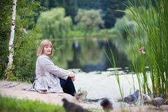 Fütterungstauben schöner Dame auf einem Seeufer Lizenzfreie Stockfotos