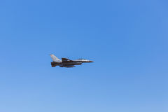 F-16在蓝天背景的军用飞机飞行 免版税库存图片