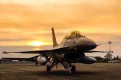 F-16猎鹰在日落背景的喷气式歼击机 免版税图库摄影