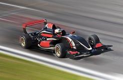 F1赛跑在与行动迷离的一条轨道的赛车 库存照片
