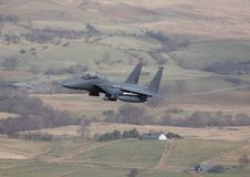 F-15 Strike Eagle. An F-15 Strike Eagle from RAF Lakenheath heads low level down a valley royalty free stock images