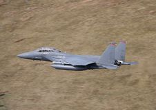 F-15 Strike Eagle. An F-15 Strike Eagle flies over the welsh countryside stock images