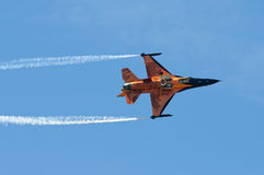 F-16 fighting falcon. Orange F-16 fighting falcon with two smoke trails against clear blue sky Royalty Free Stock Photography