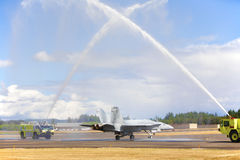 F/A-18 Hornet Pilot's Retirement Hosedown. A United States Navy F/A-18 Hornet pilot lands after his very last flight and is honored in the typical military Stock Image