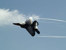 F-22 rapid turn. F-22 Raptor turns rapidly having contrail above wings Royalty Free Stock Images