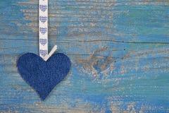 牛仔布反对蓝色木表面的心脏形状在乡村模式的f 库存图片