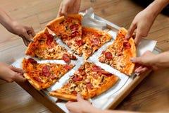 吃食物 采取薄饼切片的人们 朋友休闲,快速的F 免版税库存图片