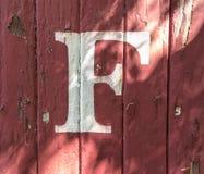 F auf rot-gemaltem hölzernem Abstellgleise stockfotos