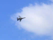 F16 falcon fighter jet flying on blue sky Stock Image