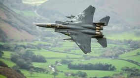 F15 fighter jet aircraft. United States Air Force USAF F15 military fighter jet aircraft against Welsh European rural landscape backdrop whilst on a low level stock photo