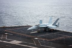 F-18 Fighter Jet on the Deck of a Carrier. F-18 military Fighter Jet on the flight deck of an Aircraft Carrier royalty free stock images