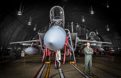 F15 fighter jet pilot in hangar. USAF F15 fighter jet pilot chats casually with a maintenance technician who's just out of frame whilst his aircraft is prepared