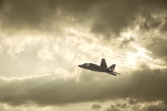 F-22 Fighter Jet. An F-22 fighter jet soars across a warm sky pierced by sun rays Royalty Free Stock Images