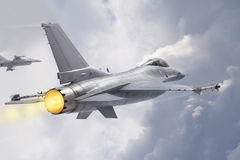 F-16 Fighting Falcon jets (models) fly through clouds Royalty Free Stock Photo