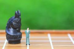 F?hrung f?r Erfolgsspiel, Miniaturgesch?ftsmannstellung auf Schachbrett- und Schachhintergrund, Strategie-Investition und Gesch?f lizenzfreies stockfoto