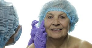 F?mea idosa de sorriso no chap?u protetor Cirurgi?o pl?stico que verifica a cara da mulher filme