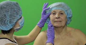 F?mea idosa de sorriso no chap?u protetor Cirurgi?o pl?stico que verifica a cara da mulher video estoque