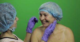 F?mea idosa de sorriso no chap?u protetor Cirurgi?o pl?stico que verifica a cara da mulher vídeos de arquivo