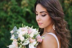 F?mea lindo no limo branco do vestido Posse bonita da menina um ramalhete das flores nas m?os imagem de stock