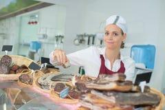 F?mea que vende a carne deliciosa do prosciutto no mercado foto de stock