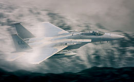 F15 Military Fighter Jet flying. Stylized F15 C military fighter jet flying of the United States Air Force flying on a low level training mission in the UK Royalty Free Stock Photo