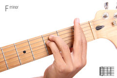 F minor guitar chord tutorial. Fm - basic minor keys guitar tutorial series. Closeup of hand playing F minor chord on guitar, isolated on white background Stock Photo