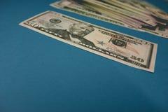 F?nfzig Dollarschein auf einem blauen Hintergrund, der durch eine Lupe studiert wird lizenzfreies stockbild
