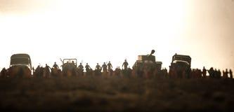 F?ngat av fientligt begrepp Milit?ra konturer och folkmassa p? bakgrund f?r krigdimmahimmel Soldater och pansarbilar f?r v?rldskr arkivbilder