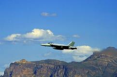 F18 que vuela cerca de las montañas fotos de archivo libres de regalías