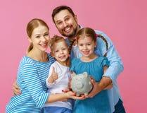 F?r familjmoder f?r finansiell planl?ggning lycklig fader och barn med spargrisen p? rosa f?rger royaltyfri bild