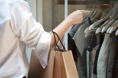 F?r innehavf?rs?ljning f?r ung kvinna p?sar f?r shopping consumerismlivsstilbegrepp i shoppinggallerian royaltyfri bild