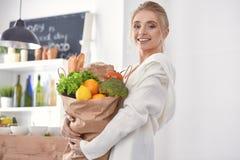 F?r innehavlivsmedelsbutik f?r ung kvinna p?se f?r shopping med gr?nsaker Standi royaltyfria bilder