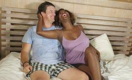 F?r?lskad kel f?r blandade etnicitetpar tillsammans hemma i s?ng med den h?rliga sk?mtsamma svarta den afrikansk amerikankvinnan  royaltyfria bilder