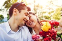 F?r?lskat krama f?r lyckliga unga par med v?rblommabuketten utomhus Beg?vad man hans flickv?n med tulpan arkivbilder