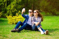 F?r?lskelse-, teknologi-, f?rh?llande-, familj- och folkbegrepp - lyckliga le unga par som tar selfie i sommar, parkerar royaltyfria foton