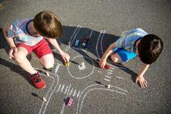 F?r siblingunge f?r tv? br?der som pojke har gyckel med bilden som drar trafikbilen med chalks Id?rik fritid f?r barn utomhus in royaltyfria foton