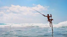 ` F?r Sri Lanka traditionell `-pinne - metodfisken som f?ngar fiskaren i Indiska oceanen, vinkar arkivfoto