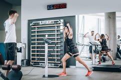 F?r stimulanskvinnor f?r EMS electro ?vningar med lagledaren i modern idrottshall royaltyfri foto