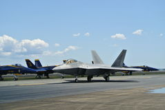 F22 Raptor and Blue Hornets Military Jets. A F22 Raptor taxiing in front of the Blue Hornets at an airshow royalty free stock photos
