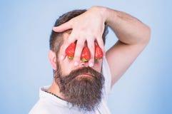 F?rblinda av jordgubben Mannen upps?kte hipsterh?llhanden med jordgubbar som var fr?msta av ?gon ?gonkast av mannen som blockeras royaltyfri fotografi