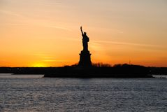 F?rbluffa sikten av statyn av frihet, p? solnedg?ngen royaltyfria foton