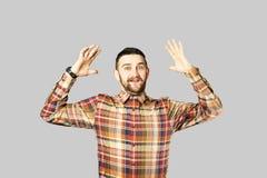 F?rdig ung man som poserar ?ver gr? bakgrund royaltyfri foto