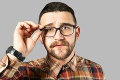 F?rdig ung man som poserar ?ver gr? bakgrund fotografering för bildbyråer