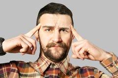 F?rdig ung man som poserar ?ver gr? bakgrund royaltyfri fotografi
